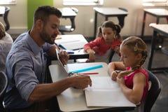 Fille de aide de jeune maître d'école avec l'étude dans la salle de classe images stock
