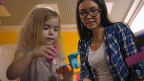 Fille de aide de professeur pour créer le jouet du constructeur banque de vidéos