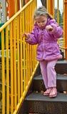 Fille de 4 ans au terrain de jeu le jour froid Image libre de droits