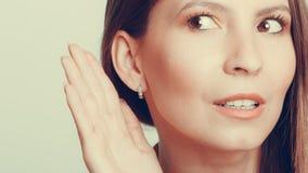 Fille de bavardage écoutant clandestinement avec la main à l'oreille Image stock