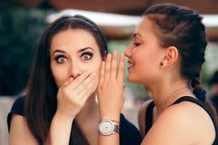 Fille de bavardage disant des secrets à son ami étonné Images stock