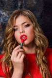 Fille de beauté appliquant le rouge à lèvres rouge Image libre de droits