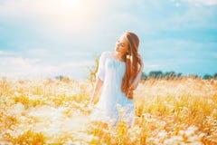 Fille de beauté appréciant dehors la nature Belle fille modèle adolescente avec de longs cheveux sains dans la robe blanche images stock