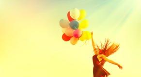 Fille de beauté courant et sautant sur le champ d'été avec les ballons à air colorés photos libres de droits