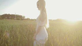 Fille de beauté courant sur le champ vert en soleil banque de vidéos