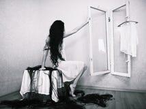 Fille de beauté cuting ses cheveux dans le fantôme vide de Halloween de pièce de crainte photographie stock