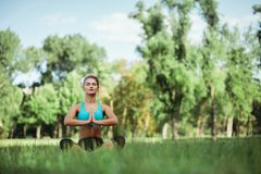 Fille de beauté de sport de forme physique faisant le yoga, forme physique et étirant l'exercice en parc Photographie stock libre de droits