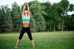 Fille de beauté de sport de forme physique faisant le yoga, forme physique et étirant l'exercice en parc Images stock