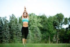 Fille de beauté de sport de forme physique faisant le yoga, forme physique et étirant l'exercice en parc, extérieur Photographie stock libre de droits