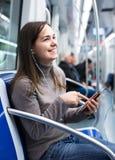 Fille de brune à l'aide du téléphone portable et souriant au souterrain Images libres de droits