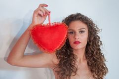 Fille de brune avec les cheveux bouclés, avec le coeur pour le jour du ` s de Valentine Photo stock