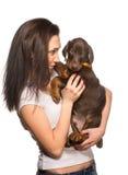 Fille de brune avec son chiot d'isolement sur le fond blanc Photographie stock libre de droits