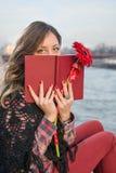 Fille de brune avec un livre par la berge Photographie stock libre de droits