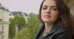 Fille de brune dans la veste noire sur le balcon appréciant les sourires spectaculaires de vue de ville dans la caméra étant heur clips vidéos