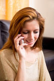 Fille de brune s'asseyant à l'appel téléphonique au sol Image stock