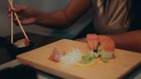 Fille de brune s'asseyant à la table dans le restaurant Sourire Mangez les sushi par des baguettes banque de vidéos