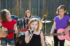 Fille de chanteur d'enfants chantant jouant la bande vivante dans l'arrière-cour Image stock