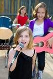 Fille de chanteur d'enfants chantant jouant la bande vivante dans l'arrière-cour Image libre de droits