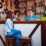 Fille de charme flirtant avec le barman et buvant un cockta court Images libres de droits
