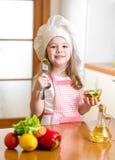 Fille de chef goûtant la nourriture saine image stock