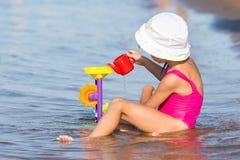 Fille de cinq ans dans le maillot de bain rose se reposant dedans sur la berge et les jeux dans les jouets de sable Photographie stock libre de droits