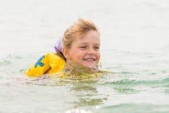 Fille de cinq ans nageant joyeux en mer dans un gilet de natation Photo stock