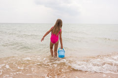 Fille de cinq ans prenant un seau de l'eau en mer photos libres de droits