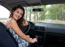 Fille de conducteur à l'intérieur de la voiture blanche regardant en arrière Photos stock