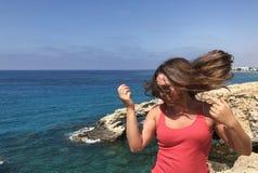 Fille de couleur claire dans un T-shirt rose sur le rivage d'un endroit populaire sur la côte de la Chypre photo libre de droits