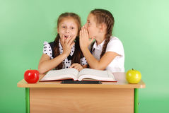 Fille de deux écoles partageant des secrets se reposant à un bureau de livre Image stock