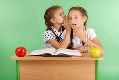 Fille de deux écoles partageant des secrets se reposant à un bureau de livre Photos stock