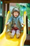Fille de deux ans heureuse dans la veste sur la glissière Photos stock