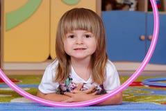 Fille de deux ans jouant et apprenant dans l'école maternelle photo stock