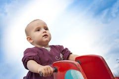 Fille de deux ans s'asseyant sur l'oscillation Image stock