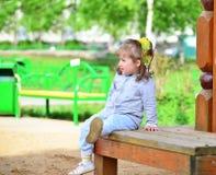 Fille de deux ans sur le banc de parc Photos stock