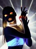 Fille de disco avec la danse de maquillage de lueur dans la lumière UV Photographie stock libre de droits
