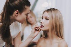 Fille de Doing Makeup Blond de maquilleur dans le salon photo libre de droits