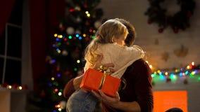 Fille de embrassement de père, donnant son cadeau de Noël, tradition de famille images stock