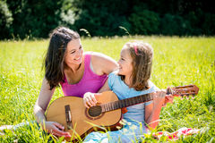 Fille de enseignement de mère jouant la guitare Photographie stock
