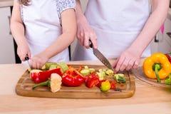 Fille de enseignement de mère pour couper des légumes photo stock