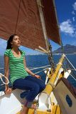 Fille de exposition au soleil sur le yacht avec les voiles rouges Photo stock