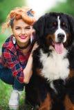 Fille de femme avec le jardin de Berne de chien au printemps Images stock