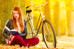 Fille de femme détendant dans le livre automnal de lecture de parc photo libre de droits