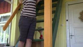 Fille de femme de peintre peignant le poteau en bois de colonne d'escalier Inclinaison  4K banque de vidéos