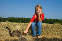 Fille de ferme et son chat. Photo stock