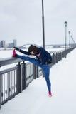 Fille de forme physique avec les espadrilles roses faisant l'étirage dehors à l'hiver de neige extérieur Photos stock