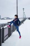 Fille de forme physique avec les espadrilles roses faisant l'étirage dehors au jour d'hiver de neige, concept de sport Photos stock