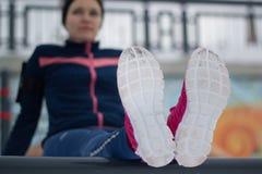 Fille de forme physique effectuant le travail vers le haut de la forme physique au parc d'hiver de neige - espadrilles au foyer Photo stock