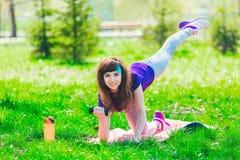 Fille de forme physique en parc et occupée dans de divers exercices avec l'haltère et le tapis la brune entre pour des sports deh Image stock