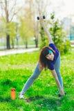 Fille de forme physique en parc et occupée dans de divers exercices avec l'haltère et le tapis la brune entre pour des sports deh Photos stock